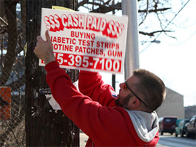 Christopher Sawyer removes a ´bandit´ sign at 6th Street and Montgomery Avenue. (Kate McCann / Staff Photographer)