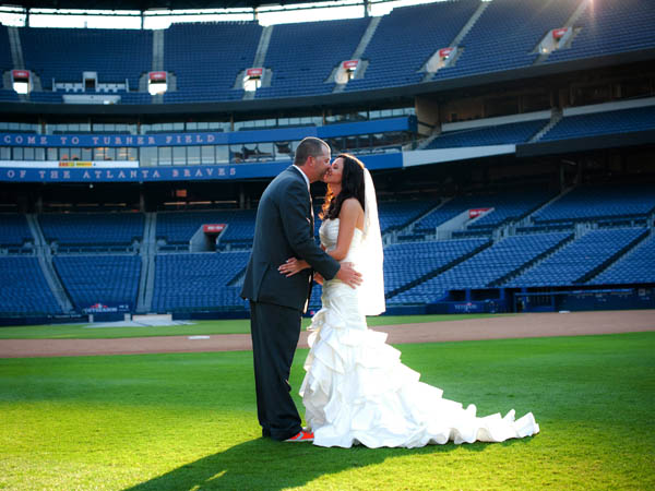 "This Nov. 3, 2012 photo released courtesy of Trisha Benzine shows Nick and Trisha Benzine at their wedding held at Turner Field in Atlanta. Some couples, find that the massive stadiums where they enjoy hearing the crack of the bat can also be the perfect place to hear their beloved say, ""I do."" (AP Photo/Graceology Photography)"