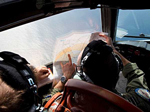 Flight Lt. Jayson Nichols looks at a map as he flies aboard a Royal Australian Air Force AP-3C Orion aircraft during a search operation of the missing Malaysian Airlines flight MH370 over the southern Indian Ocean, Thursday, March 27, 2014. Planes and ships searching for debris suspected of being from the downed Malaysia Airlines jetliner failed to find any Thursday before bad weather cut their hunt short in a setback that came as Thailand said its satellite had spotted even more suspect objects. (AP Photo/Michael Martina, Pool)