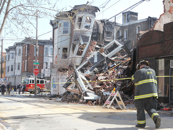 A firefighter walks by the ruins of the building at Fitzwater and S. 4th St. a day after a fire killed fire Capt. Mike Goodwin and left 2 other fire fighters injured on April 6, 2013.  ( CHARLES FOX / Staff<br />Photographer )