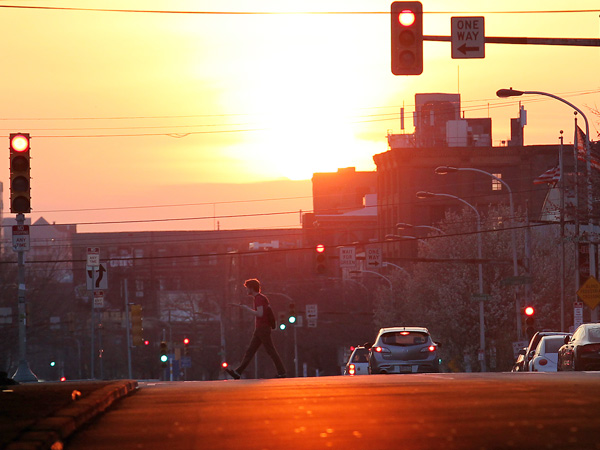 A pedestrian walks across Spring Garden Street on Second Street, as the sun sets on Monday, April 8, 2013.  ( Yong Kim / Staff Photographer )