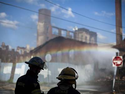 Firefighters view the aftermath of a fire in a warehouse on York Street near Kensington Avenue in Philadelphia on Monday, April 9, 2012. Two firefighters died after a wall collapsed on them while they fought the massive early-morning blaze. (AP Photo/Matt Rourke)