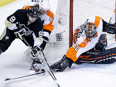 Ilya Bryzgalov pokes the puck away from the Penguins´ Pascal Dupuis in the second period on Friday. (Gene J. Puskar/AP)