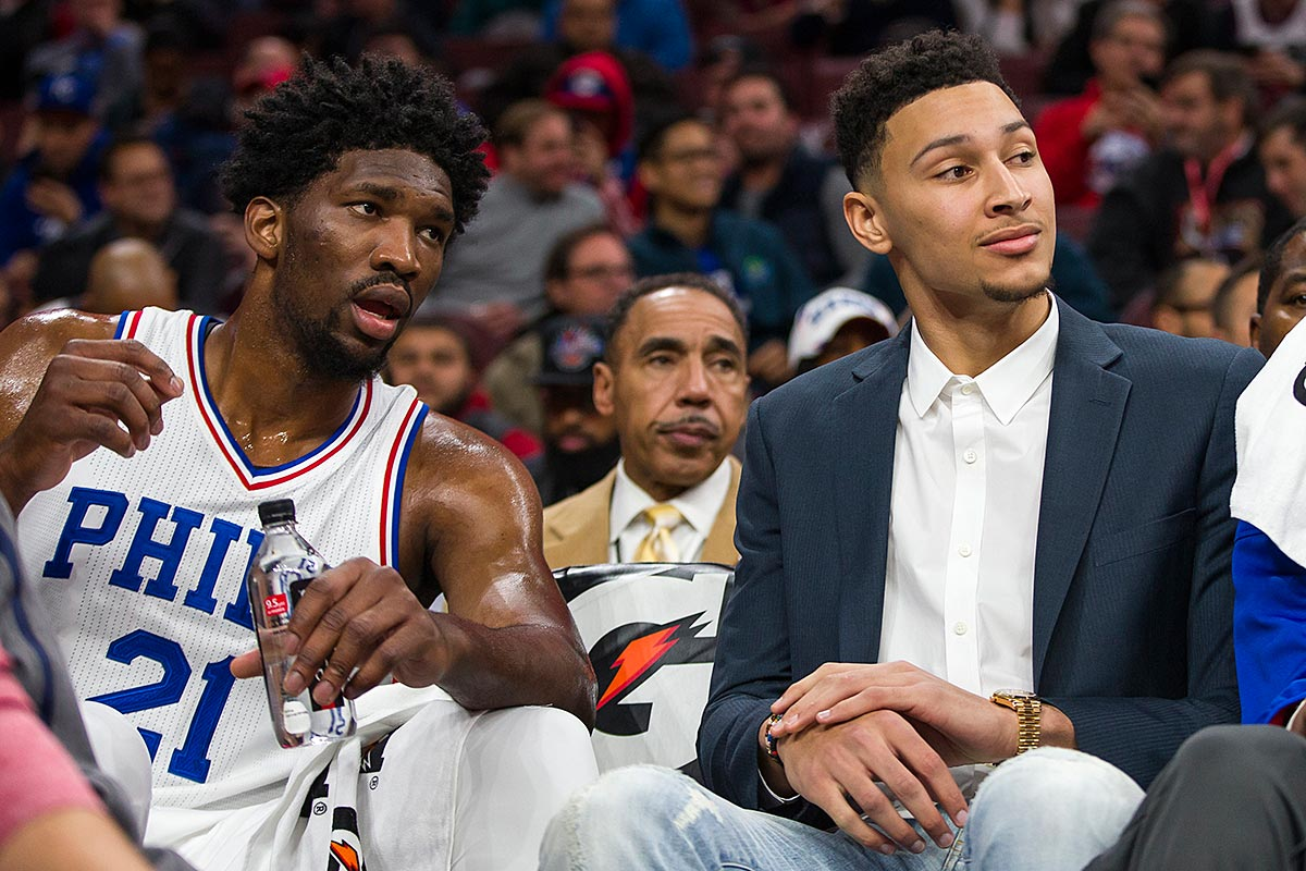 Philadelphia 76ers center Joel Embiid, left, looks on from the bench with Ben Simmons, right, during the first half of an NBA basketball game against the Toronto Raptors, Wednesday, Dec. 14, 2016, in Philadelphia. The Raptors won 123-114.