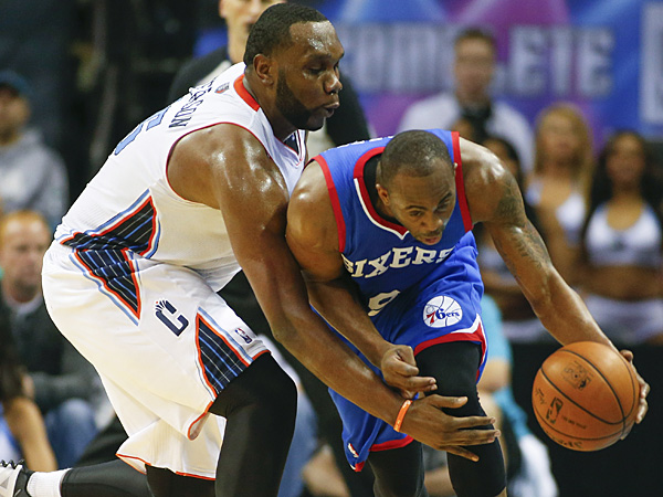 76ers guard James Anderson, right, works to control the ball as Bobcats center Al Jefferson, left, plays defense during the second half. (Chris Keane/AP)