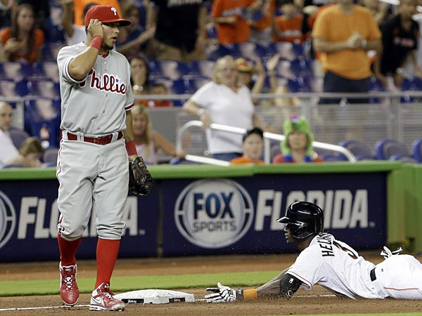 Miami Marlins&acute; Adeiny Hechavarria (3) slides safely into third base<br />after batting a triple as Philadelphia Phillies&acute; Freddy Galvis (13)<br />awaits the late throw against during the fifth inning of a baseball<br />game in Miami, Saturday, April 13, 2013. (AP Photo/Alan Diaz)