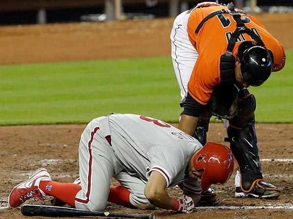Miami Marlins catcher Miguel Olivo, top, attends Philadelphia<br />Phillies&acute; Freddy Galvis after Galvis was hit by a pitch during the<br />eighth  inning of a baseball game in Miami, Sunday, April 14, 2013.<br />Galvis was able to continue playing. The Phillies won 2-1. (AP<br />Photo/Alan Diaz)
