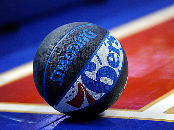 A basketball with the 76ers logo rests on the court at the Wells Fargo Center. (Michael Perez/AP)