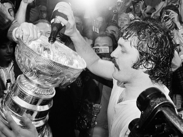 Flyers goalie Bernie Parent pours champagne into the Stanley Cup after the Flyers defeated Boston in the 1974 Stanley Cup finals. Parent was named MVP of the playoffs. (AP file photo)