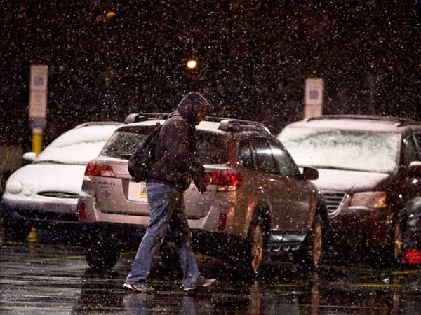 A man walks to a store in Shamokin, Northumberland County, as snow falls the evening of Tuesday, April 15, 2014. Small amounts of snow were reported throughout central and eastern Pennsylvania. (AP Photo/The News-Item, Larry Deklinski)