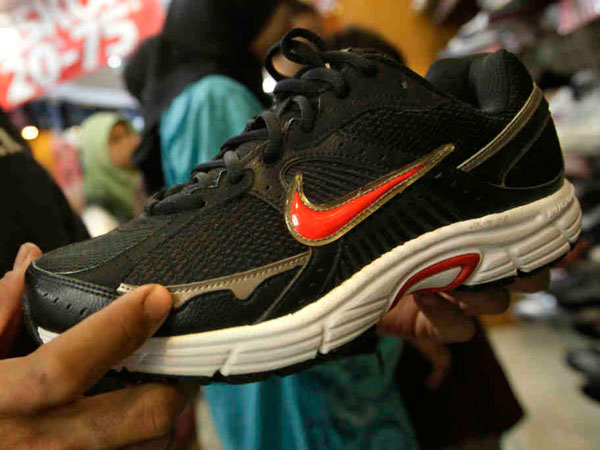 "In this May 17, 2011 photo, an Indonesian man inspects a Nike shoe at a store in Jakarta, Indonesia. Workers for a Nike contractor in Indonesia say they´ve been physically and verbally abused for several years, with supervisors calling them ""dogs,"" slapping them in the face, or hurling sneakers across the factory floor almost every day. (AP Photo/Dita Alangkara)"