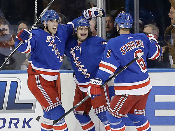 The Rangers´ Derick Brassard, left, and Anton Stralman, right, celebrate with Mats Zuccarello after Zuccarello scored a goal during the first period against the Philadelphia Flyers in Game 1 of an NHL hockey first-round playoff series on Thursday, April 17, 2014, in New York. (Frank Franklin II/AP)