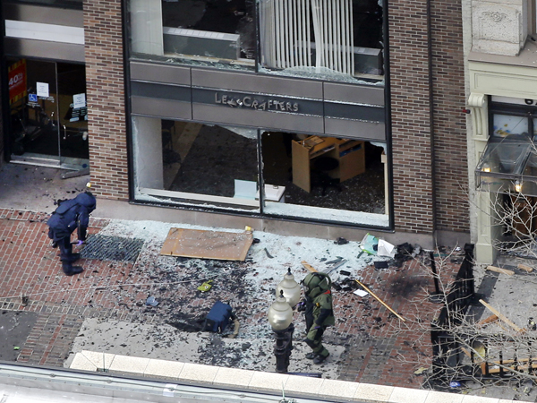 One of the blast sites on Boylston Street near the finish line of the 2013 Boston Marathon is investigated by two people in protective suits in the wake of two blasts in Boston Monday, April 15, 2013. (AP Photo/Elise Amendola)