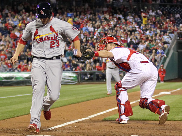 The Cardinals´ David Freese scores on a seventh-inning sacrifice fly ball past Phillies´ catcher Erik Kratz on Thursday, April 18, 2013. (Yong Kim/Staff Photographer)