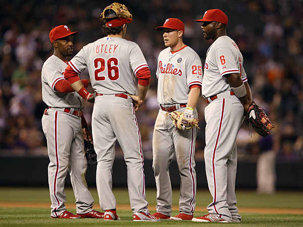 Infielders Jimmy Rollins #11, Chase Utley #26, Cody Asche #25 and Ryan Howard #6 of the Philadelphia Phillies of the Philadelphia Phillies await a pitching change in the seventh inning at Coors Field on April 18, 2014 in Denver, Colorado. (Photo by Doug Pensinger/Getty Images)