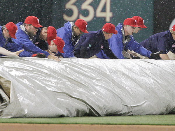 Ground crew pulls a tarp to cover the field during a rain delay with the during the 7th inning at Citizens Bank Park in Philadelphia, Thursday, April 19, 2013. (Steven M. Falk/Staff Photographeer)