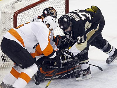 Ilya Bryzgalov and Andreas Lilja go after the loose puck against Penguins forward Evgeni Malkin. (Yong Kim/Staff Photographer)