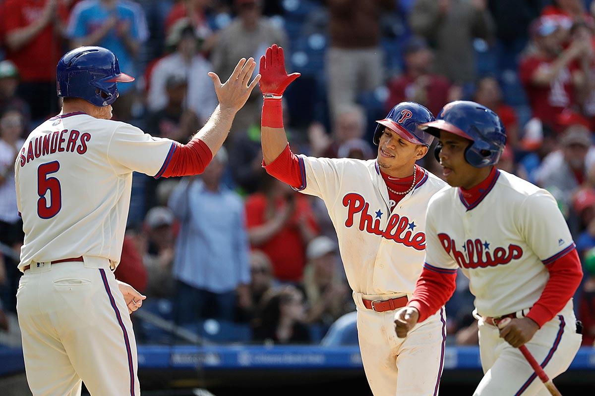 Philadelphia Phillies´ Cesar Hernandez, center, and Michael Saunders, left, celebrate after Hernandez´s two-run home run during the eighth inning of a baseball game against the Atlanta Braves, Sunday, April 23, 2017, in Philadelphia.