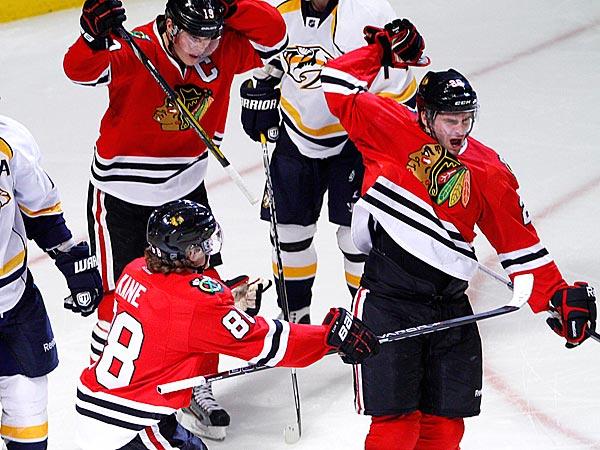 Blackhawks players Patrick Kane and Jonathan Toews help celebrate a goal. (AP Photo/Charles Cherney)