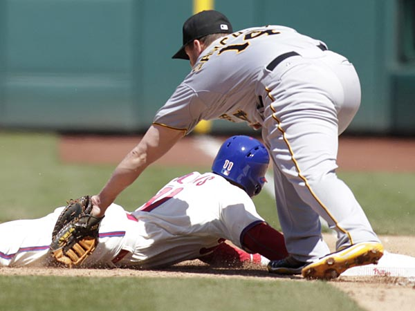 Pittsburgh Pirates´ Gaby Sanchez (14) miss plays a pickoff attempt on  Philadelphia Phillies´ Jimmy Rollins in the third inning of a baseball game, Thursday, April 25, 2013, in Philadelphia. Rollins is safe at second. Watching at right is first base umpire Mike Muchlinski. (AP Photo/H. Rumph Jr)