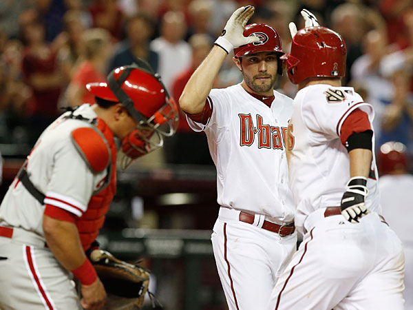 The Diamondbacks´ Aaron Hill, right, gets a high-five from teammate A.J. Pollock, second from right, after Hill hit a 2-run home run, as Philadelphia Phillies´ Carlos Ruiz, left, looks away during the fourth inning of a baseball game on Friday, April 25, 2014, in Phoenix. (Ross D. Franklin/AP)