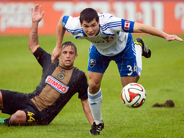Impact´s Karl Ouimette, right, is brought down by Philadelphia Union´s Danny Cruz during the first half of an MLS soccer game in Montreal, Saturday, April 26, 2014. (AP Photo/The Canadian Press, Graham Hughes)