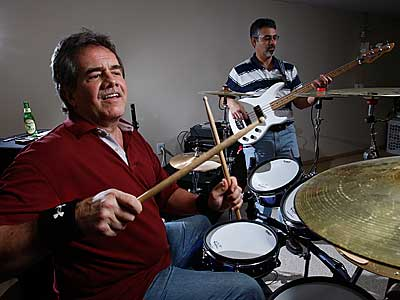 Jay Strunk (left), an unemployed executive, drums during a jam with bass guitar player Gerry Franciosa (right). Strunk says the band helps his relieve some of the stress that he has because of his unemployment. ( Michael S. Wirtz / Staff Photographer )