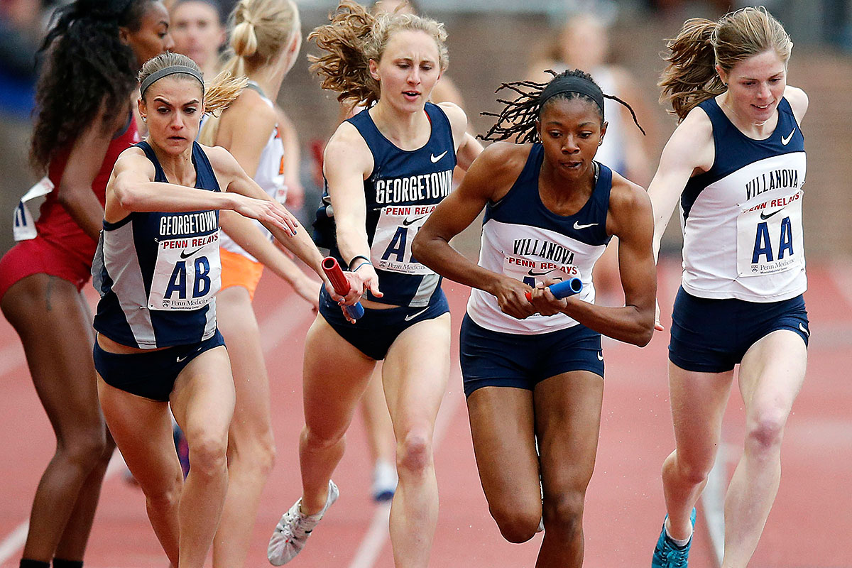 Villanova&acute;s Sidney Hayes (second right) holds the baton from teammate<br />Siofra Cleirigh Buttner (far right) as Georgetown&acute;s Heather Martin (far left) receives the baton form teammate Andrea Keklak (second left) in the second leg of the Penn Relays College Women&acute;s Distance Medley Championship of America Invitational.