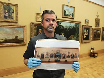 Tim Gerschick, a Barnes Museum art handler/collections assistatnt, holds his reference photo for the upstaris gallery at the new Barnes Collections Gallery in Philadelphia. Tim uses these photographs from the Merion Gallery to place the artwork back in exactly the same place position in the new galleries downtown.  ( MICHAEL BRYANT / Staff Photographer )