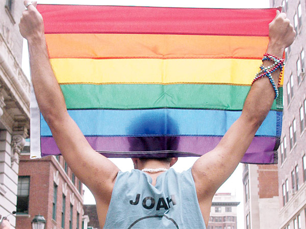 Jason Brendel holds a rainbow flag, representing diversity and LGBT equality. (Rebecca Barger)