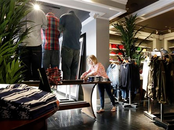 In this Thursday, March 28, 2013, photo, a woman works at an Abercrombie & Fitch store in Chicago. The government reports how much consumers spent and earned in March on Monday, April 29, 2013. (AP Photo/Nam Y. Huh)