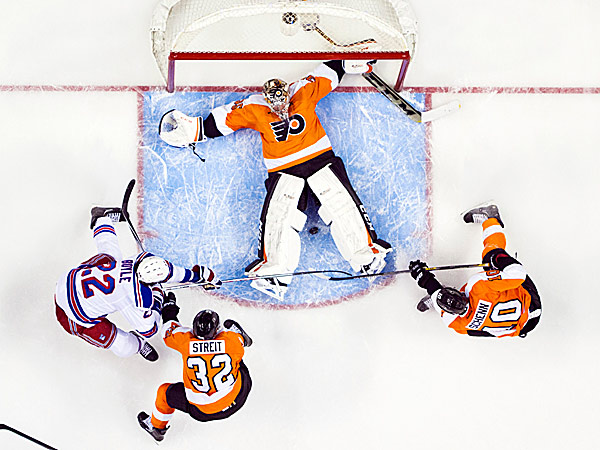 Flyers goalie Steve Mason tries to keep the puck between his legs as Brayden Schenn and the Rangers´ Brian Boyle go after it with the Flyers´ Mark Streit defending. (Chris Szagola/AP)