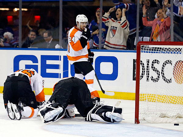 Steve Mason and Zac Rinaldo sit on the ice as Matt Read skates past them after the Rangers´ Benoit Pouliot scores. (Yong Kim/Staff Photographer)