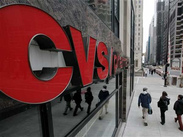 FILE - In this Feb. 7, 2012 file photo, pedestrians walk past a CVS store in Chicago. (AP Photo/M. Spencer Green, File)