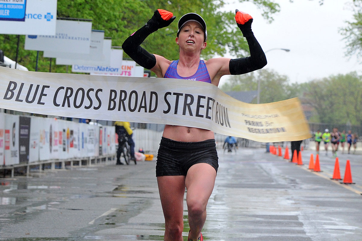 Crystal Burnick of Skippack crosses the finish line at the Navy Yard as the women´s winner at the 2016 Blue Cross Broad Street Run.