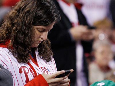 Fans check their cell phones during the Phillies vs. Mets game, Sunday, May 1, 2011. News broke during the game that Osama bin Laden had been killed. (AP Photo/Matt Slocum)