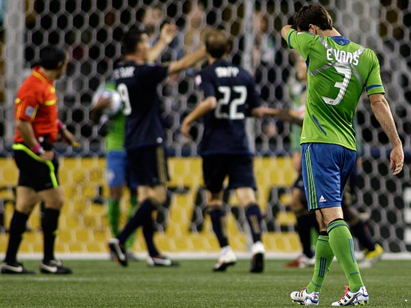 Seattle Sounders FC´s Brad Evans (3) reacts as Philadelphia Union players celebrate a goal scored by Brian Carroll in the second half of a MLS soccer match, Saturday, Oct. 8, 2011, in Seattle. The Union beat the Sounders, 2-0. (AP Photo/Ted S. Warren)