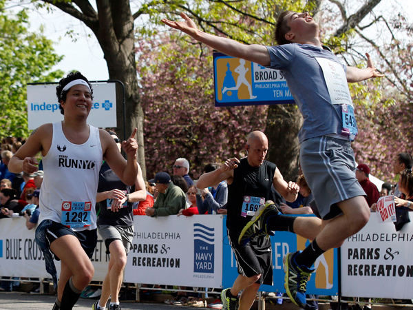 Stephen Armstrong leaps at the finish line as Luis Gonzalez points to Armstrong at the Navy Yard.  (Yong Kim/Staff Photographer)