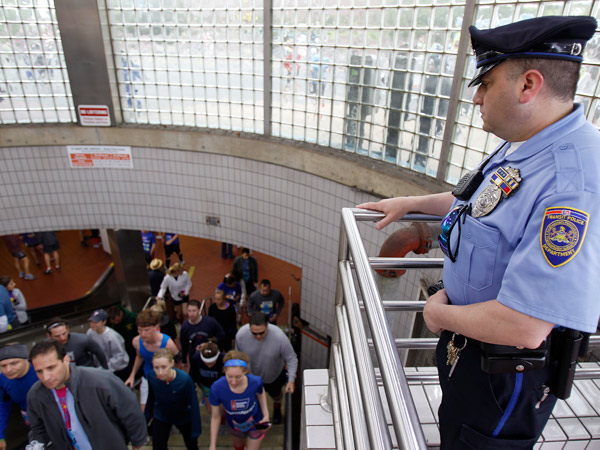 Transit Officer Douglas Ioven is accused of handcuffing a woman who tried to file a complaint against him after an argument inside a Dunkin' Donuts Christmas morning. In this file photo, he watches as people exit the Olney subway stop. (David Maialetti / Staff Photographer/File)