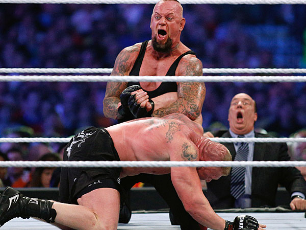 The Undertaker, top, and Brock Lesnar wrestle during Wrestlemania XXX at the Mercedes-Benz Super Dome in New Orleans on Sunday, April 6, 2014. (Jonathan Bachman/AP Images for WWE)