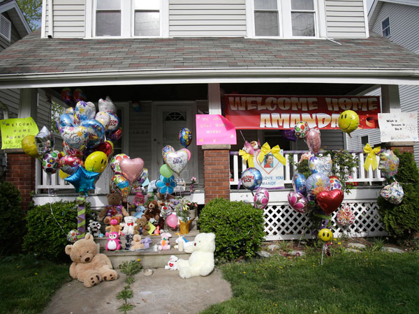 The front porch of Amanda Berry&acute;s home is decorated with balloons and signs on Wednesday, May 8, 2013, in Cleveland. Berry, 27, Michelle Knight, 32, and Gina DeJesus, had apparently been held captive in a house since their teens or early 20s, police said. (AP Photo/Tony<br />Dejak)