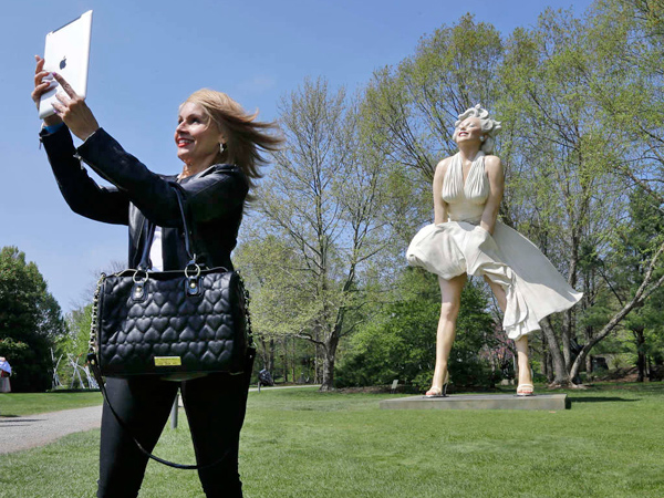 Johanna Bianchi of Freehold, N.J., took a photo of herself Sunday with the larger-than-life Marilyn Monroe. (Mel Evans / AP)