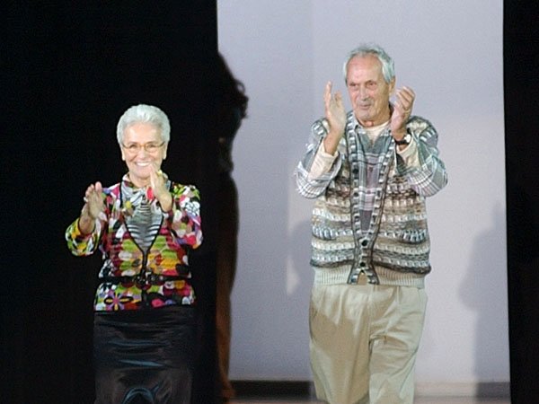 FILE - In this Oct. 2003 file photo Rosita, left, and Ottavio Missoni take the catwalk after presenting their Spring/Summer 2004 fashion collection, in Milan, Italy. Italian fashion company Missoni says its co-founder, Ottavio Missoni, has died in his home earlier on Thursday, May 9, 2013 in northern Italy. Missoni, who was 92, founded the iconic fashion brand of zigzagged-patterned knitwear along with his wife, Rosita, in 1953. The Missonis are a family fashion dynasty, with the coupleís children and their offspring involved in expanding the brand. (AP Photo/Antonio Calanni, File)