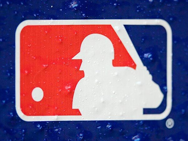 Rain drops fall on a Major League Baseball logo seen on the Baltimore Orioles dugout before Game 2 of the American League division baseball series between the Orioles and the New York Yankees on Monday, Oct. 8, 2012, in Baltimore. (AP Photo/Nick Wass)