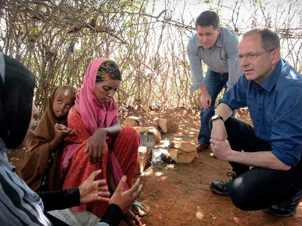 Andrew Witty (right), GlaxoSmithKline CEO, and Justin Forsyth, Save the Children CEO, in Kenya with Aisha, 25, and daughter Leila, 5. (Sven Torfinn / Save the Children)