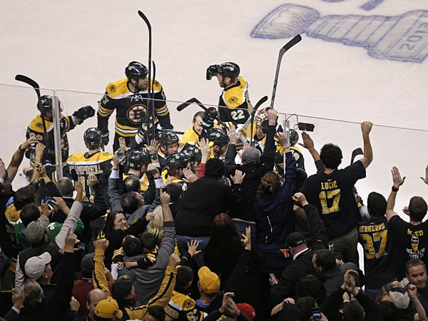 Fans and teammates celebrate as they swarm around Boston Bruins center Patrice Bergeron, who scored the game winning goal off Toronto Maple Leafs goalie James Reimer during overtime, in Game 7 of their NHL hockey Stanley Cup playoff series in Boston, Monday, May 13, 2013. The Bruins won 5-4. (AP Photo/Charles Krupa)