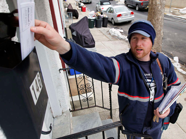 This file photo shows a letter carrier delivering mail in Philadelphia. Last year, 28 mail carriers were attacked by dogs. (AP file photo)