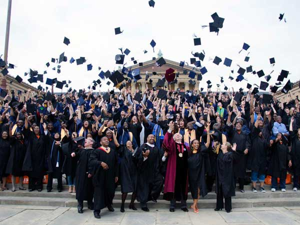 Philadelphia Mayor Michael A. Nutter joins 300 college graduates from 15 local universities in tossing their caps in the air for a photo on the steps of the Philadelphia Museum of Art earlier this month. Several schools have moved today´s graduation ceremonies inside due to expected heavy rain showers. (RACHEL WISNIEWSKI / Staff Photographer)