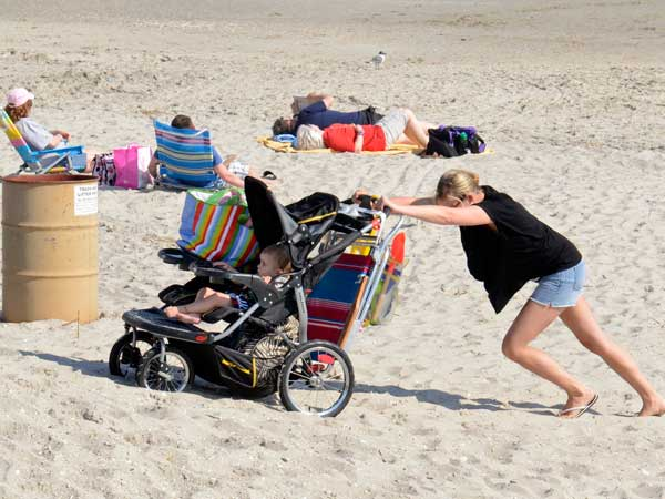 Jamie Finn of Atco pushes son 2-1/2 year old son Wes up off the beach after spending the day in Ocean City on their third day trip to the shore during an unseasonably warm week in April. TOM GRALISH / Staff Photographer )