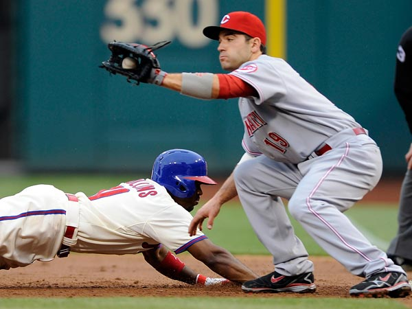 Jimmy Rollins (left) dives back to first base and beats the tag from Cincinnati Reds´ Joey Votto (19) in the third inning of a baseball game on Saturday, May 18, 2013, in Philadelphia. (Michael Perez/AP)